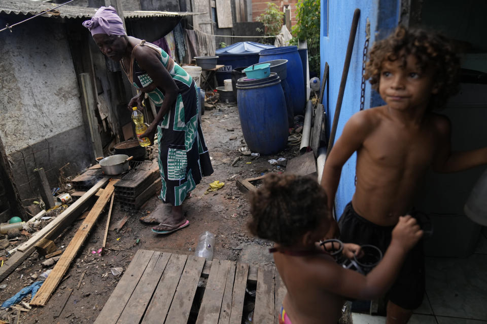Lady Laurentino, 74, cooks in a wood fire near her home in the Jardim Gramacho favela of Rio de Janeiro, Brazil, Monday, Oct. 4, 2021. With the surge in cooking gas prices, Laurentino says she is cooking with wood because she doesn't have money to buy another cooking gas cylinder. (AP Photo/Silvia Izquierdo)