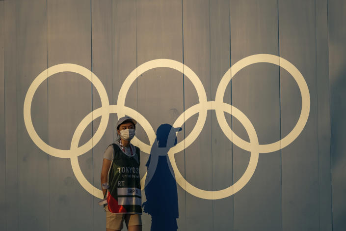 FILE - In this July 22, 2021, file photo, a volunteer walks past the Olympic rings ahead of the 2020 Summer Olympics, on Thursday, in Tokyo Japan. (AP Photo/Petros Giannakouris, File)