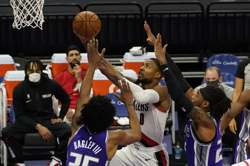 Portland Trail Blazers guard Damian Lillard, right, goes to the basket between Sacramento Kings' Marvin Bagley III, left, and Richaun Holmes, right, during the first quarter of an NBA basketball game in Sacramento, Calif., Wednesday, Jan. 13, 2021. (AP Photo/Rich Pedroncelli)