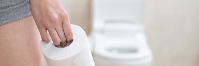 woman holding a roll of toilet paper and walking into the bathroom
