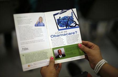 A woman reads a pamphlet in Spanish at a health insurance enrollment event in Cudahy