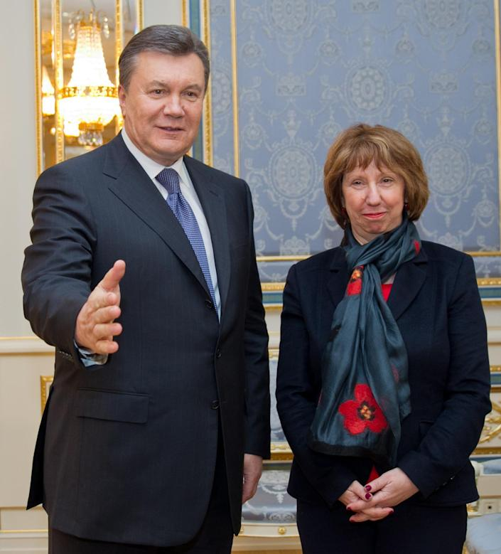 Ukrainian President Viktor Yanukovych, left, greets EU foreign policy chief Catherine Ashton in Kiev, Ukraine, Tuesday, Dec. 10, 2013. Top Western diplomats headed to Kiev Tuesday to try to defuse a stand-off between President Viktor Yanukovych's government and thousands of demonstrators, following a night in which police in riot gear dismantled protesters' encampments outside government buildings. Demonstrators have occupied the Ukrainian capital for weeks opposing Yanukovych's decision to freeze ties with the European Union and tilt to Russia instead. (AP Photo/ Andrei Mosienko, Pool)