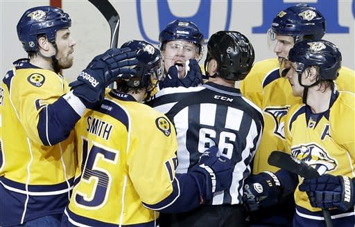Linesman Darren Gibbs (66) checks on Nashville Predators right wing Patric Hornqvist, of Sweden, top center, after Hornqvist was hit in the face while scoring a goal against the Dallas Stars in the second period of an NHL hockey game on Monday, Feb. 25, 2013, in Nashville, Tenn. (AP Photo/Mark Humphrey)