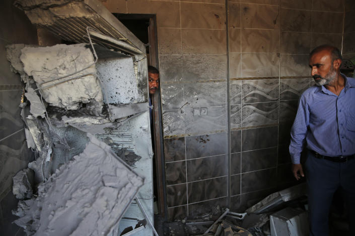 Halil Tokak, right, the neighborhood chief and another resident, inspect the damage on a house, caused by a mortar fired from inside Syria, on the Turkish town of Akcakale, southeastern Turkey, Saturday, Oct. 12, 2019. Nobody got hurt by the attack as the owners of the house were not at home at the time of the attack. (AP Photo/Lefteris Pitarakis)