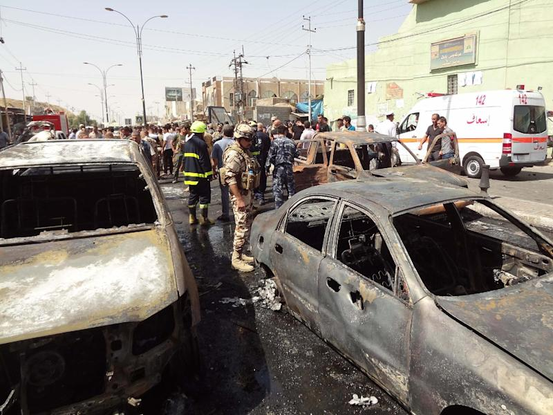 Iraqi onlookers and security forces stand next to burnt cars following a motorcycle bombing attack which killed at least 8 people in the northern city of Kirkuk on September 19, 2014