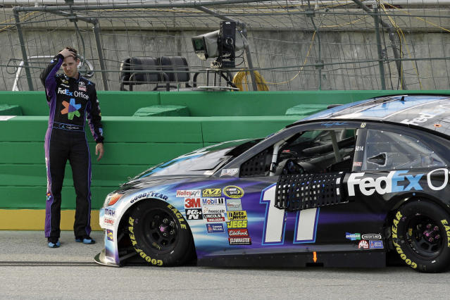 Denny Hamlin reacts after seeing the damage to the right side of his car following a collision with the outside wall during the NASCAR Sprint Cup series auto race Saturday, June 28, 2014, at Kentucky Speedway in Sparta, Ky. The accident put Hamlin out of the race. (AP Photo/Garry Jones)