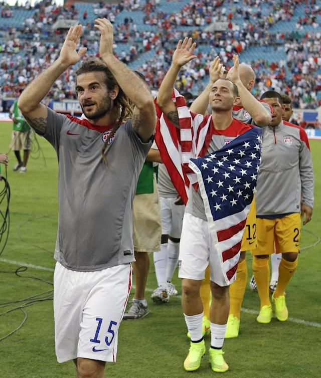 United States's Kyle Beckerman (15), Brad Davis, second from left, and other team members applaud fans as the come off the field after defeating Nigeria 2-1 in an international friendly soccer match in Jacksonville, Fla., Saturday, June 7, 2014. (AP Photo/John Raoux)