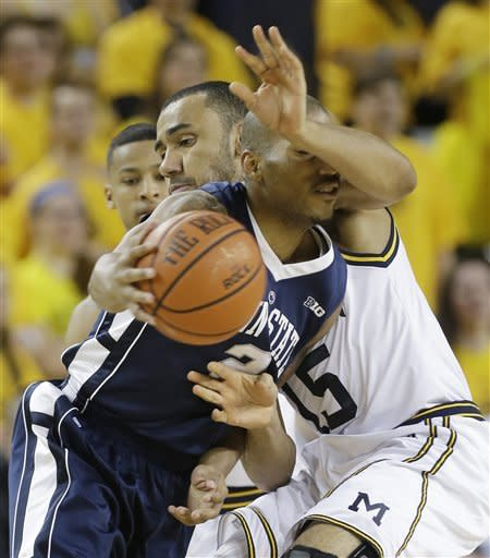Penn State guard D.J. Newbill (2) is defended by Michigan forward Jon Horford (15) during the second half of an NCAA college basketball game at Crisler Center in Ann Arbor, Mich., Sunday, Feb. 17, 2013. (AP Photo/Carlos Osorio)