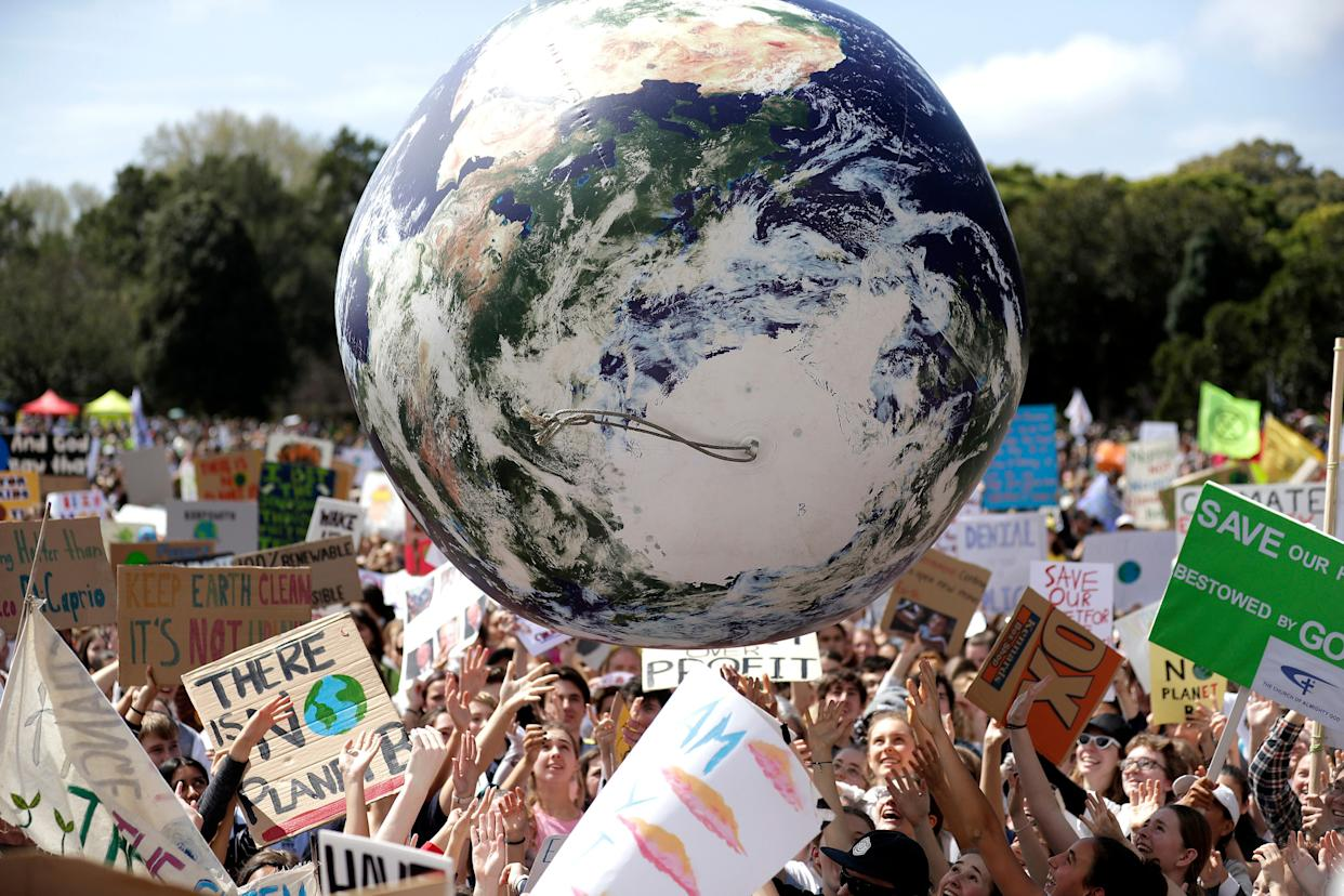 A large inflatable globe is bounced through the crowd as thousands of protestors, many of them students, gather in Sydney, Friday, Sept. 20, 2019. (AP Photo/Rick Rycroft) (Photo: ASSOCIATED PRESS)