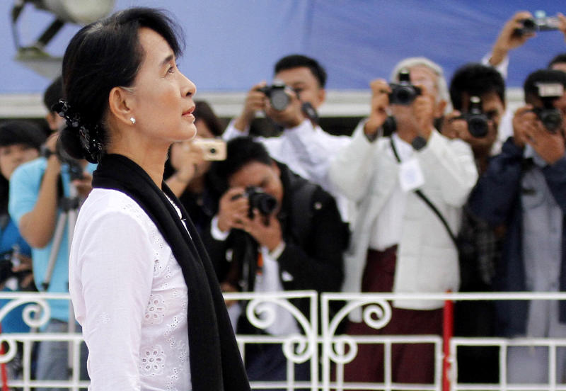Myanmar opposition leader Aung San Suu Kyi, center, salutes the tomb of her late father Gen. Aung San during a ceremony to mark the 65th anniversary of his 1947 assassination, at the Martyrs' Mausoleum in Yangon, Myanmar on Thursday, July 19, 2012.  For the first time in decades, Myanmar state television broadcast the memorial ceremony for the country's independence hero, the latest sign of change in the former pariah nation. (AP Photo/Khin Maung Win)