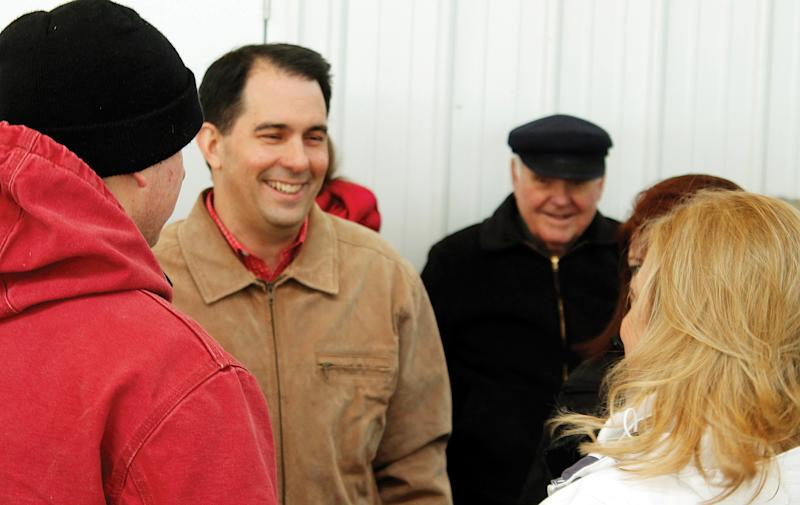Wisconsin Gov. Scott Walker speaks with constituents before signing his half-billion dollar property and income tax bill at March at Horsens Homestead Farms March, 24, 2014, in Cecil, Wis. For individual taxpayers, the measure amounts to a $131 reduction on a median-valued home's tax bill this December and saves the average worker $46 in annual income taxes. (AP Photo/The Shawano Leader, Lee Pulaski)
