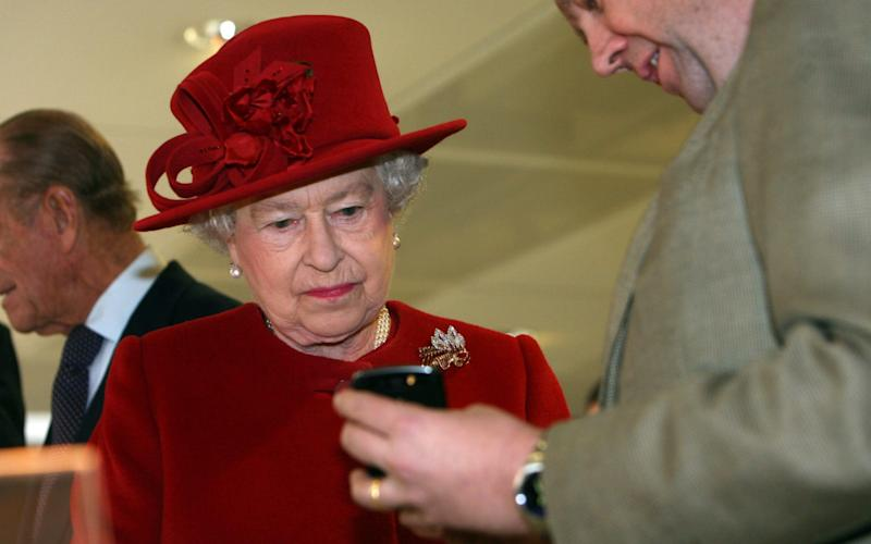 The Queen looks at a mobile telephone - PAUL GROVER