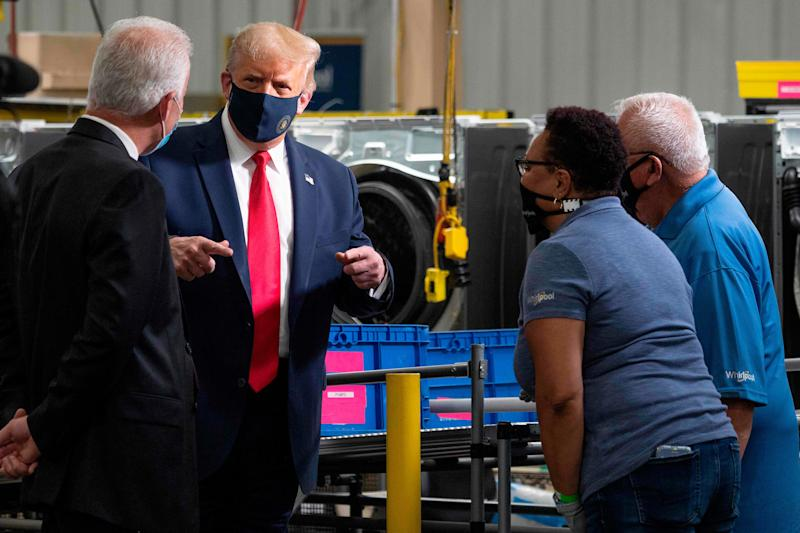 President Donald Trump wears a face mask as he speaks to employees on a tour of the Whirlpool manufacturing plant in Clyde, Ohio.