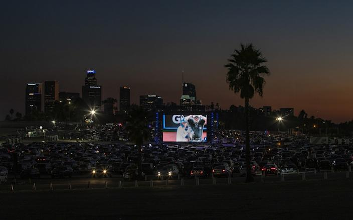 Dodger fans watch the World Series from their cars on big screens set up in the Dodger Stadium parking lot