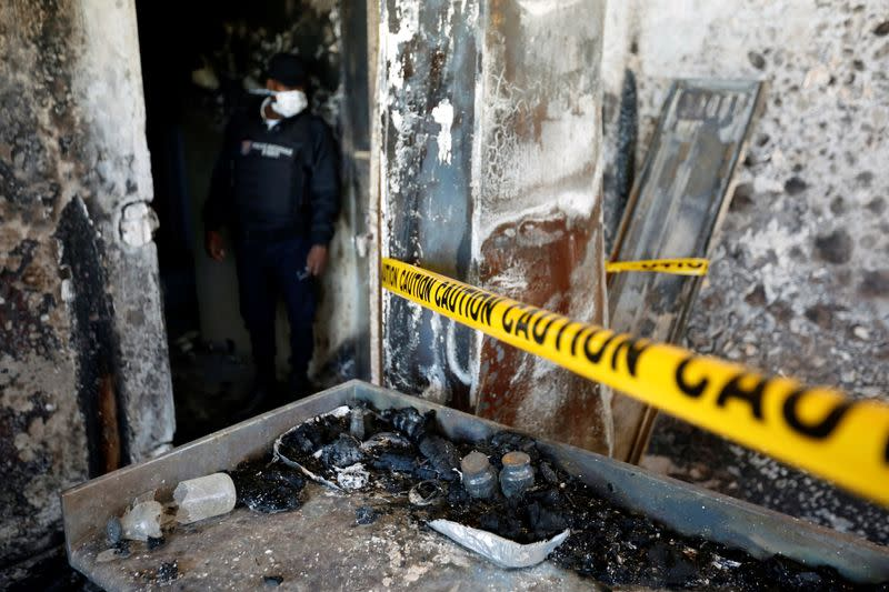 A police officer looks at burnt debris at an orphanage after it was partially destroyed in a fire, in Port-au-Prince
