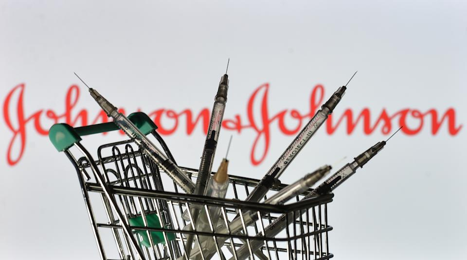 Medical syringes in the mini shopping trolley are seen in front of the Johnson and Johnson logo displayed on a screen. On Friday, 28 May 2021, in Dublin, Ireland. (Photo by Artur Widak/NurPhoto via Getty Images)