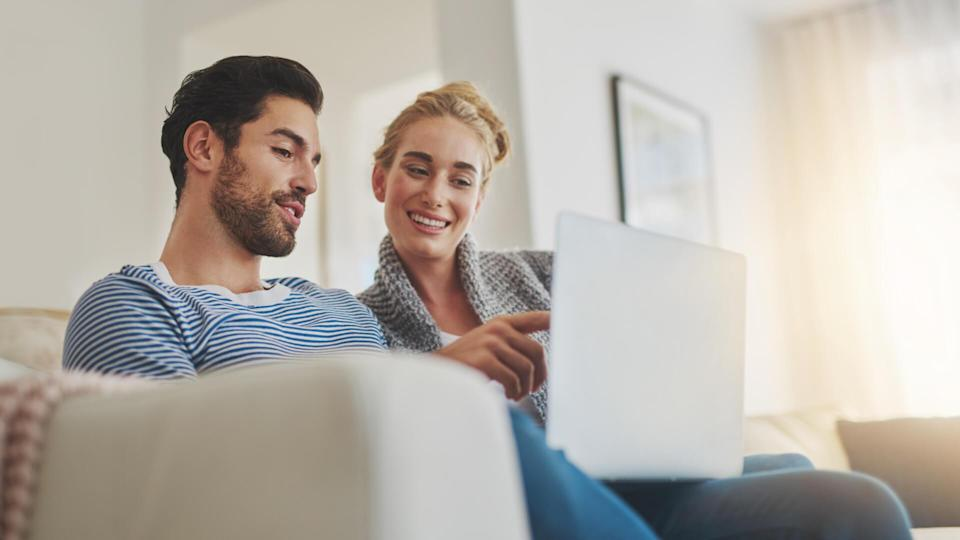 Shot of a young couple using a laptop on their sofa at home.