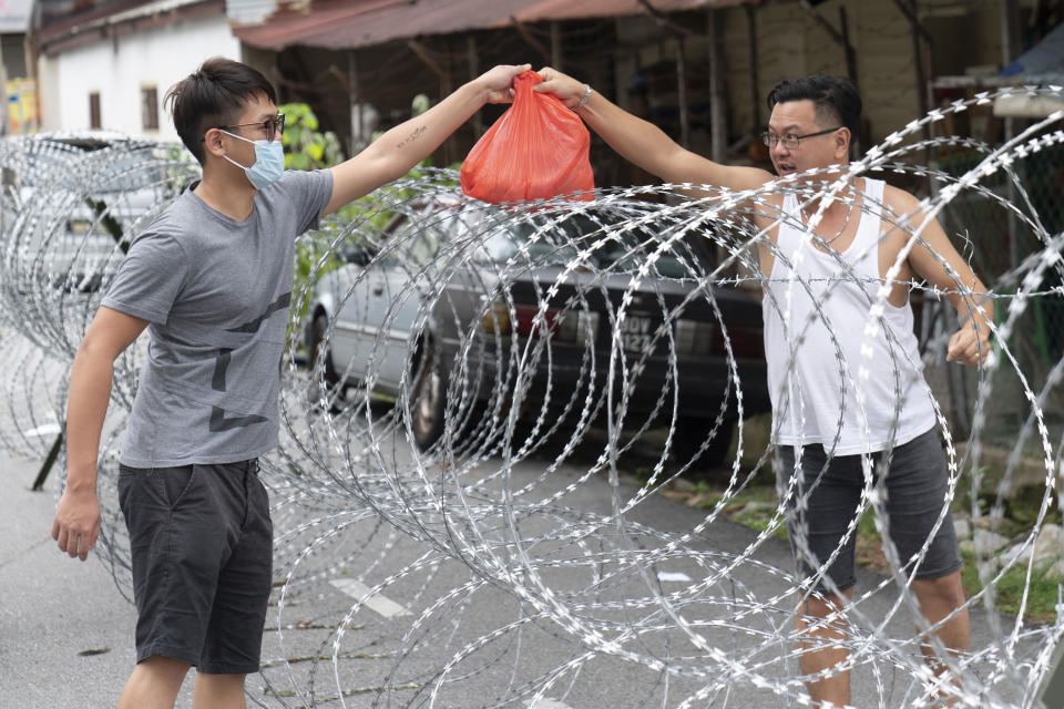 A man collect supplies over barbed wire in the coronavirus locked down area of Selayang Baru, outside of Kuala Lumpur, Malaysia, on Sunday, April 26, 2020. The lockdown was implemented to allow authorities to carry out screenings to help curb the spread of coronavirus. (AP Photo/Vincent Thian)