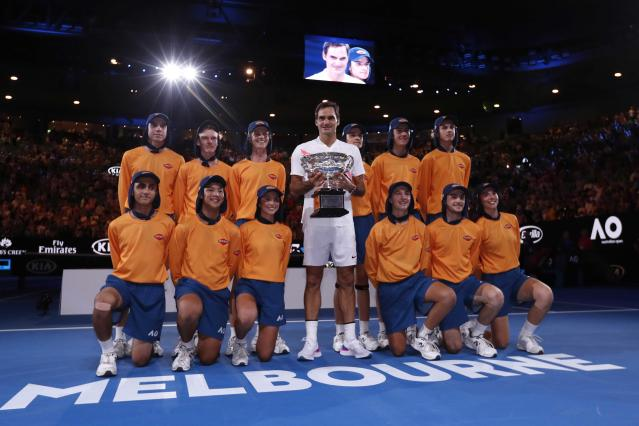 Tennis - Australian Open - Men's singles final - Rod Laver Arena, Melbourne, Australia, January 28, 2018. Switzerland's Roger Federer celebrates with the trophy as he poses with ball boys and girls after winning the final against Croatia's Marin Cilic. REUTERS/Issei Kato