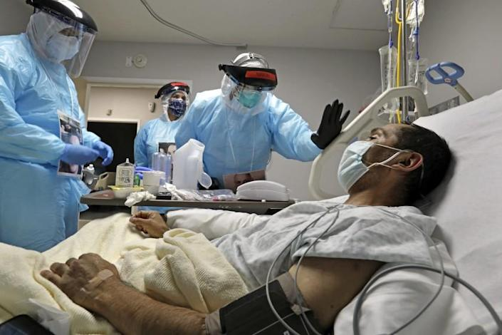 HOUSTON, TEXAS-MAY 6, 2020-Dr. Joseph Varon, the doctor in charge of the COVID-19 unit at United Memorial Medical Center in north Houston, checks on COVID patient Melquiades Cervantes, 43, who was hoping to be released this week. (Carolyn Cole/Los Angeles Times)
