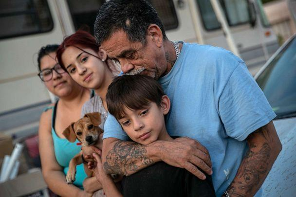 PHOTO: The Medrano family sit outside their RV on Oct. 07, 2020, in Phoenix. They narrowly avoided eviction from the RV park earlier in the day. (John Moore/Getty Images)