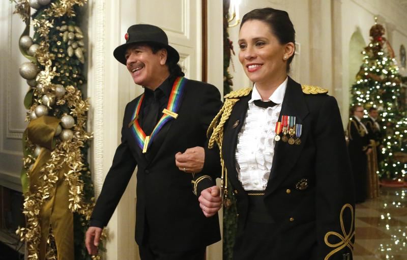 Musician Santana is escorted as he arrives with fellow Kennedy Center honorees for a reception at the White House in Washington