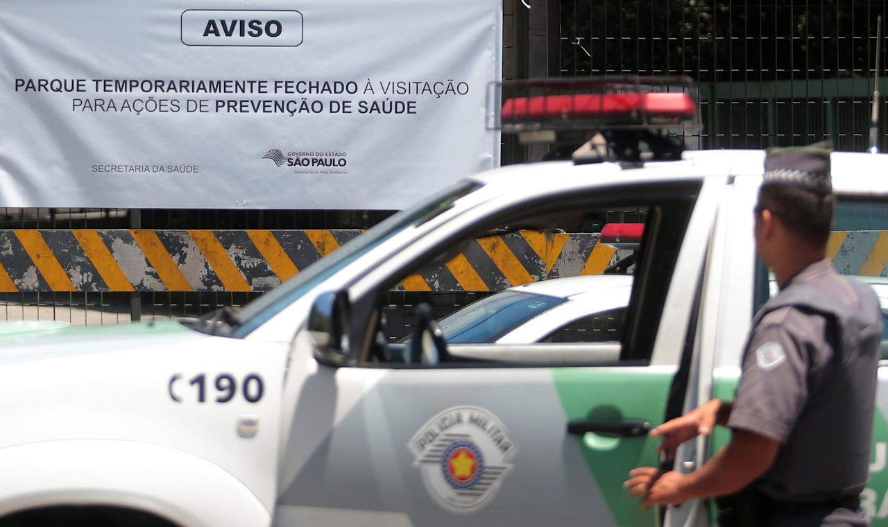 """An environmental police officer stands guard in front of the main entrance of Sao Paulo's Zoo in Sao Paulo, Brazil January 23, 2018. The sign reads: """"Park temporarily closed for visitation for preventive health actions."""" REUTERS/Leonardo Benassatto NO RESALES. NO ARCHIVES"""
