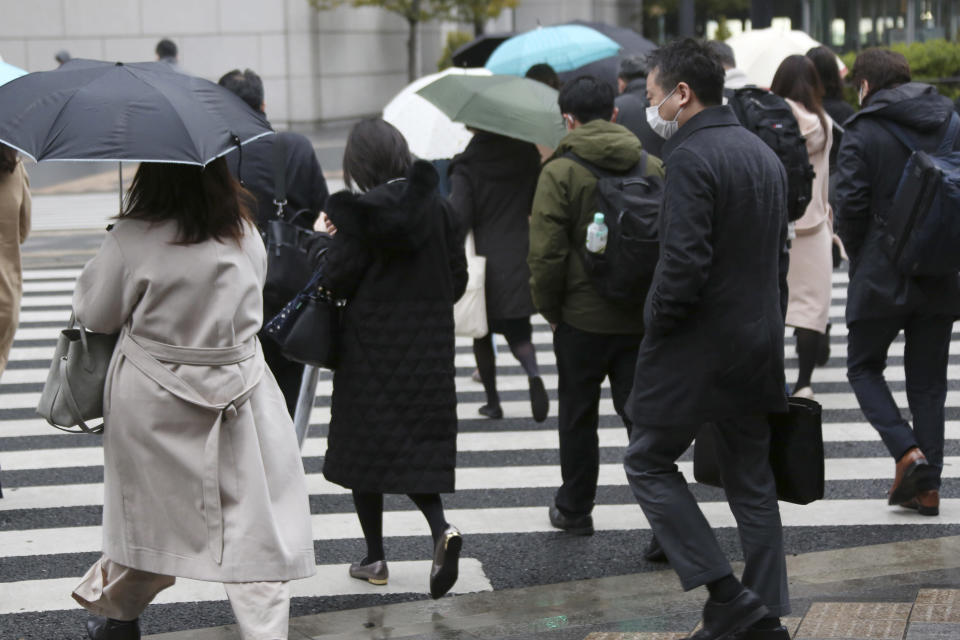 People wearing face masks to protect against the spread of the coronavirus walk at a crossing in Tokyo, Monday, Feb. 15, 2021. The Japanese economy grew at an annual rate of 12.7% in October-December, marking the second straight quarter of growth, amid a recovery from the slump caused by the coronavirus pandemic, according to government data released Monday. (AP Photo/Koji Sasahara)