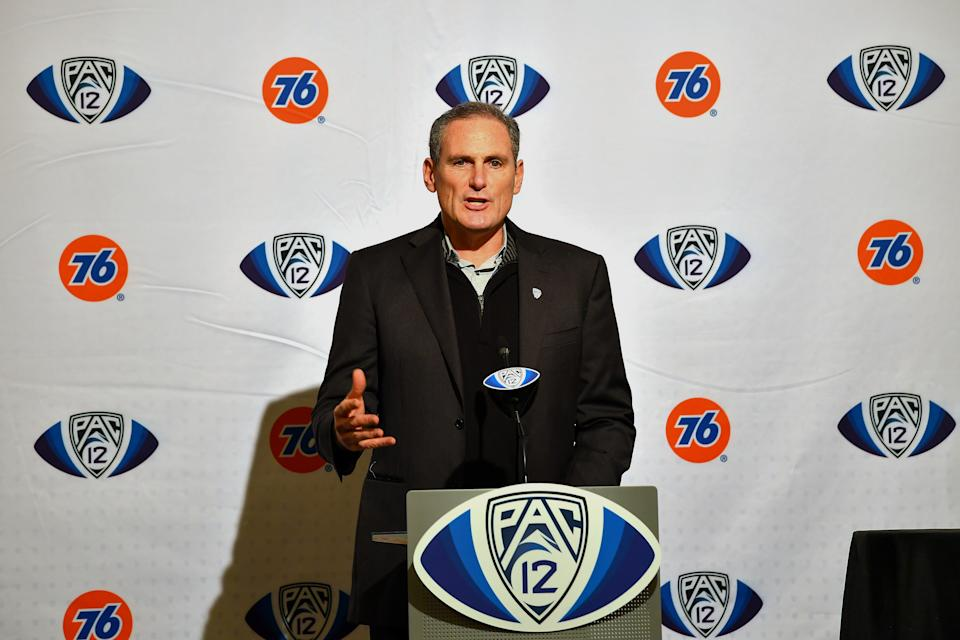 Larry Scott talks at a podium.