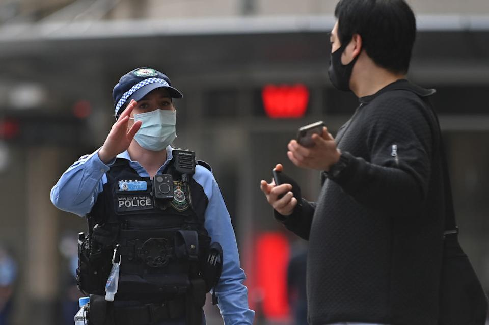 Police officers check ID cards of people walking in the CBD in order to prevent an anti-lockdown protest, during lockdown in Sydney, Australia, Saturday.