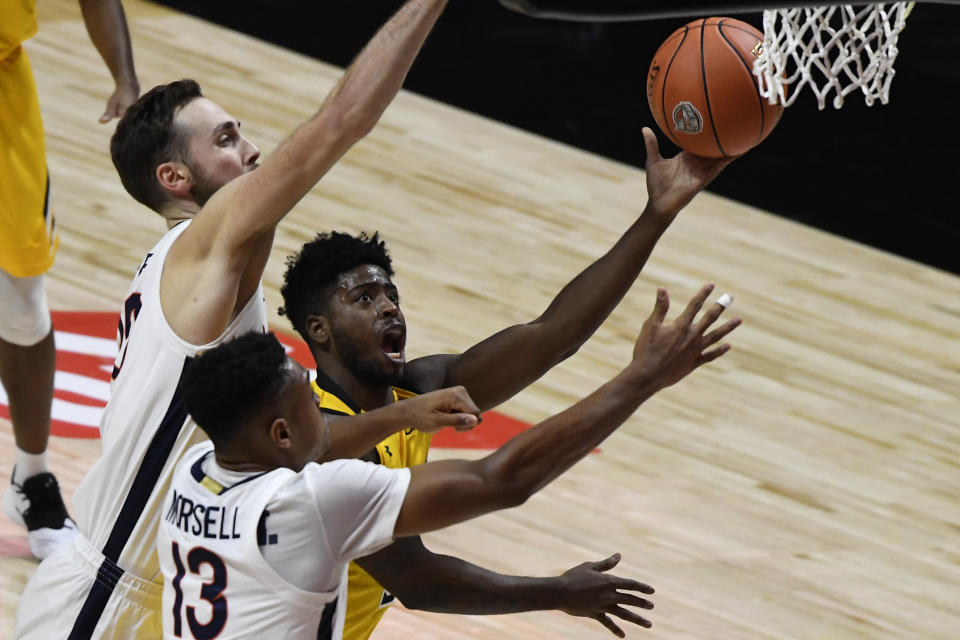 Towson's Cam Allen, center, shoots between Virginia's Jay Huff, left, and Virginia's Casey Morsell, right, in the first half of an NCAA college basketball game, Wednesday, Nov. 25, 2020, in Uncasville, Conn. (AP Photo/Jessica Hill)