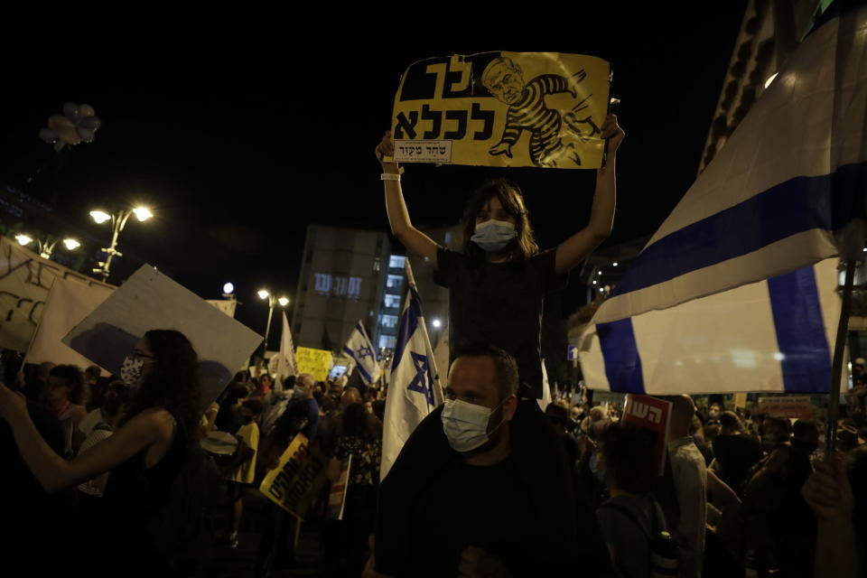 "Israelis hold signs and chant slogans during a demonstration against Israeli Prime Minister Benjamin Netanyahu near the Prime Minister's residence in Jerusalem, Saturday, Aug. 15, 2020. Hebrew reads:""go to prison ""(AP Photo/Sebastian Scheiner)"