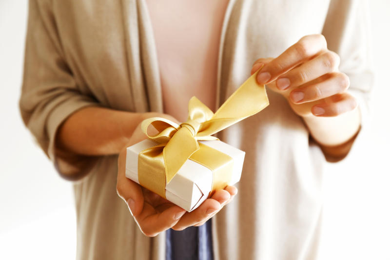 Young casual woman wearing pink shirt and long beige cardigan holding a beautiful present in shiny wrapping tied with golden bow. Unwrapping gift concept. Background, copy space, close up.