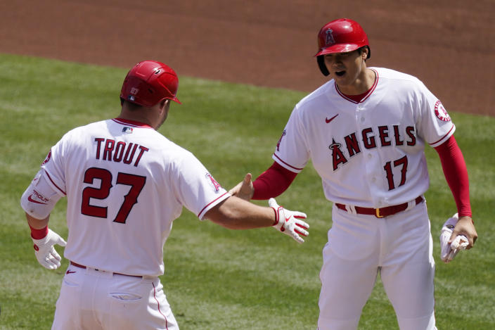 Los Angeles Angels' Mike Trout, left, is congratulated by Shohei Ohtani after hitting a two-run home run during the first inning of a baseball game against the Houston Astros Tuesday, April 6, 2021, in Anaheim, Calif. (AP Photo/Mark J. Terrill)