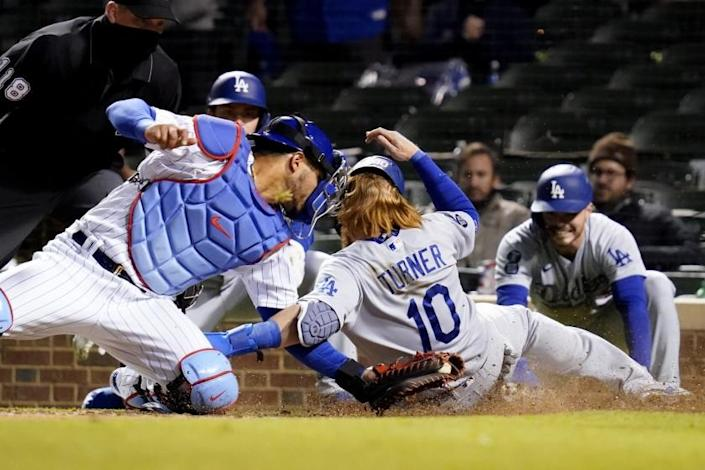 Chicago Cubs catcher Willson Contreras, left, tags out Los Angeles Dodgers' Justin Turner at home during the 10th inning of a baseball game in Chicago, Wednesday, May 5, 2021. (AP Photo/Nam Y. Huh)