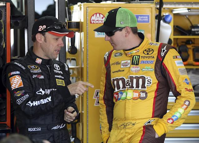 Drivers Matt Kenseth, left, and Kyle Busch talk before practice for Saturday's NASCAR Sprint Cup series auto race at Charlotte Motor Speedway in Concord, N.C., Friday, May 16, 2014. (AP Photo/Bob Jordan)