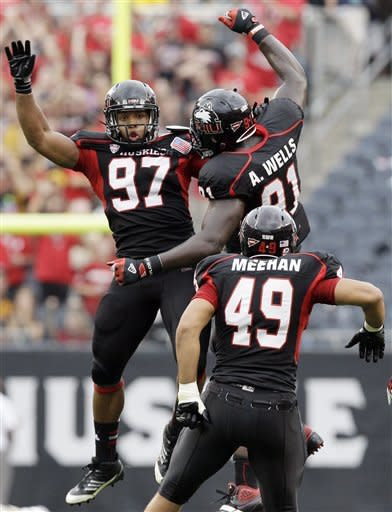 Northern Illinois defensive end Joe Windsor (97) celebrates with defensive tackle Anthony Wells (91) and defensive end Jason Meehan (49) after Windsor sacked Iowa quarterback James Vandenberg (16) during the first half of an NCAA college football game at Soldier Field in Chicago, Saturday, Sept. 1, 2012. (AP Photo/Nam Y. Huh)