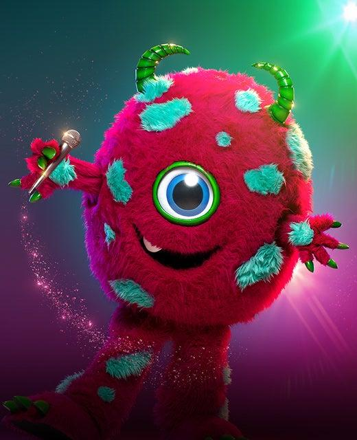 Promo picture of The Monster from the  TV show The Masked Singer holding a microphone. The Monster has one eye, is red with teal spots and horns.