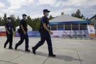 Security guards past near a checkpoint to the China International Fair for Trade in Services (CIFTIS) to be held in Beijing on Friday, Sept. 4, 2020. As China recovers from the COVID-19 pandemic, business as usual is picking back up with the holding of the China International Fair for Trade in Services. Nearly 2,000 Chinese and foreign enterprises will participate and showcase their newest technology in public health and digital technology (AP Photo/Ng Han Guan)