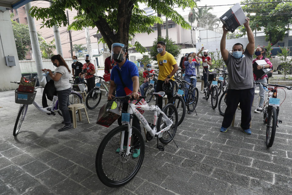 Recipients of the Benjamin Canlas Courage to be Kind Foundation react after getting their bicycles outside a building at the financial district of Manila, Philippines, Saturday, July 11, 2020. Restricted public transportation during the lockdown left many Filipinos walking for hours just to reach their jobs. The foundation saw the need and gave away mountain bikes to nominated individuals who are struggling to hold on to their jobs in a country hard hit by the coronavirus. (AP Photo/Aaron Favila)