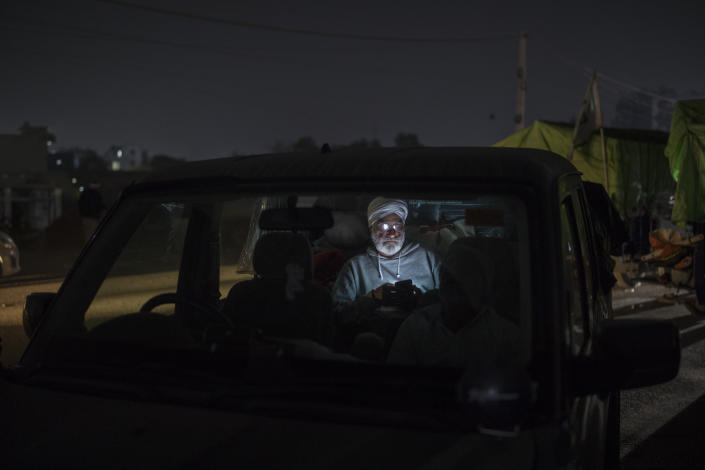 """Farmer Avtar Singh, 70, looks at his mobile phone as he sits inside his SUV parked on a highway during a protest at the Delhi-Haryana state border, India, Wednesday, Dec. 2, 2020. The convoy of trucks, trailers and tractors stretches for at least three kilometers (1.8 miles). It's a siege of sorts and the mood among the protesting farmers is boisterous. Their rallying call is """"Inquilab Zindabad"""" (""""Long live the revolution""""). (AP Photo/Altaf Qadri)"""