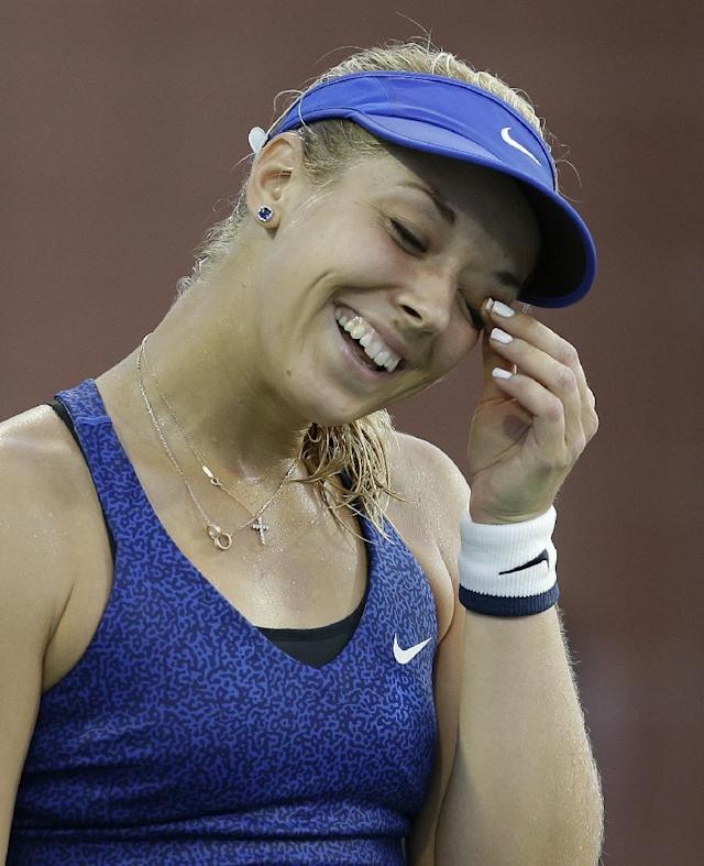 Sabine Lisicki, of Germany, laughs after missing a shot against Madison Brengle, of the United States, during the second round of the U.S. Open tennis tournament Wednesday, Aug. 27, 2014, in New York. (AP Photo/Darron Cummings)