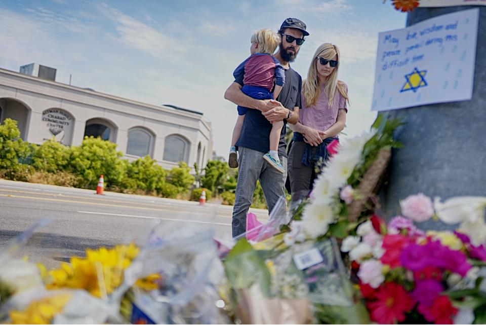 Mourners look over a make-shift memorial across the street from the Chabad of Poway Synagogue on Sunday, April 28, 2019 in Poway, California, one day after a teenage gunman opened fire, killing one person and injuring three others including the rabbi as worshippers marked the final day of Passover, authorities said. (Sandy Huffaker/AFP via Getty Images)