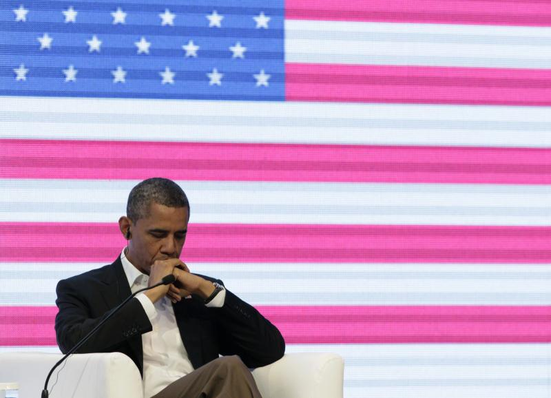 President Barack Obama sits in front of a large video screen displaying an image of a U.S. national flag during a three-way conversation with Brazil's President Dilma Rousseff and Colombia's President Juan Manuel Santos, not pictured, at the CEO Summit of the Americas in Cartagena, Colombia, Saturday April 14, 2012. Regional business leaders are meeting parallel to the sixth Summit of the Americas which brings together presidents and prime ministers from Canada, the Caribbean, Latin America and the U.S. (AP Photo/Carolyn Kaster)