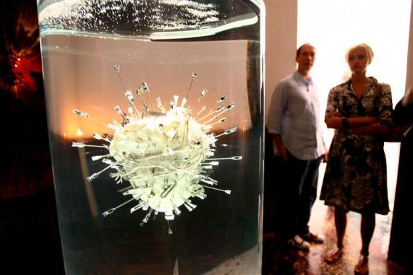 "Visitors to the Hilario Galguera gallery in Mexico City contemplate a piece by Damien Hirst titled ""The Sacred Heart of Jesus"" consisting of a bulls heart pierced with assorted surgical instruments suspended in formaldehyde February 23, 2006."