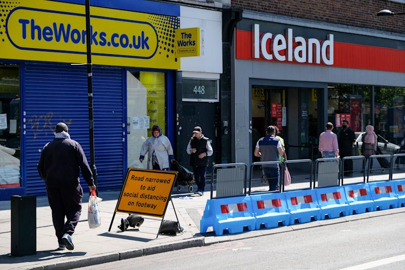 A road in north London is narrowed to aid social distancing while shoppers queue for a supermarket (Photo: Barcroft Media via Getty Images)