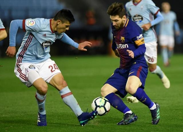Barcelona's forward Lionel Messi (R) vies with Celta Vigo's defender Facundo Roncaglia during the Spanish league football match between RC Celta de Vigo and FC Barcelona at the Balaidos stadium