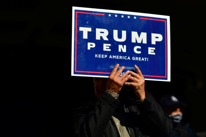 A Trump supporter clutches a campaign sign with both hands after Democratic presidential nominee Joe Biden overtook President Donald Trump in Philadelphia