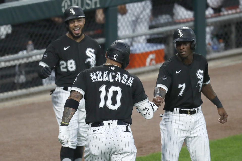 Chicago White Sox's Yoan Moncada (10) is greeted outside the dugout by Leury Garcia (28) and Tim Anderson, after Moncada's three-run home run off Minnesota Twins starting pitcher Jose Berrios during the second inning of a baseball game Friday, July 24, 2020, in Chicago. (AP Photo/Charles Rex Arbogast)