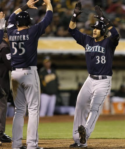 Seattle Mariners' Michael Morse, right, celebrates with Michael Saunders (55) after Morse hit a three-run home run off Oakland Athletics' Jarrod Parker in the third inning of a baseball game Tuesday, April 2, 2013, in Oakland, Calif. (AP Photo/Ben Margot)